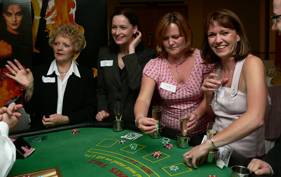 Corporate guests enjoying the dealer's company at the Blackjack Table during a James Bond Casino Party